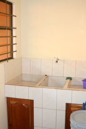 "The laundry room includes a typical three-part tiled built-in sink or ""pila."""