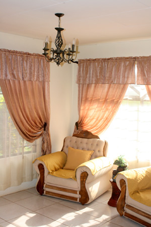 Large windows and high cheilings with chandeliers provide a pleasant ambiance in the living room and other rooms.